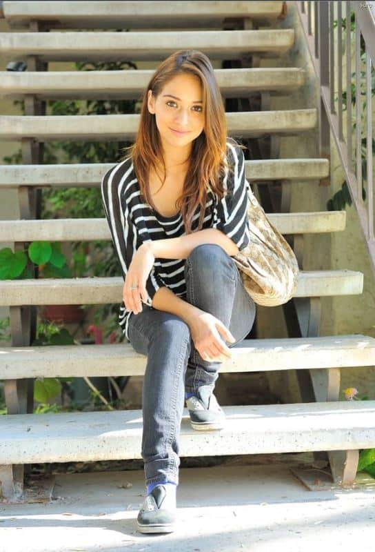Christie sitting on stairs outside in jeans and striped shirt.