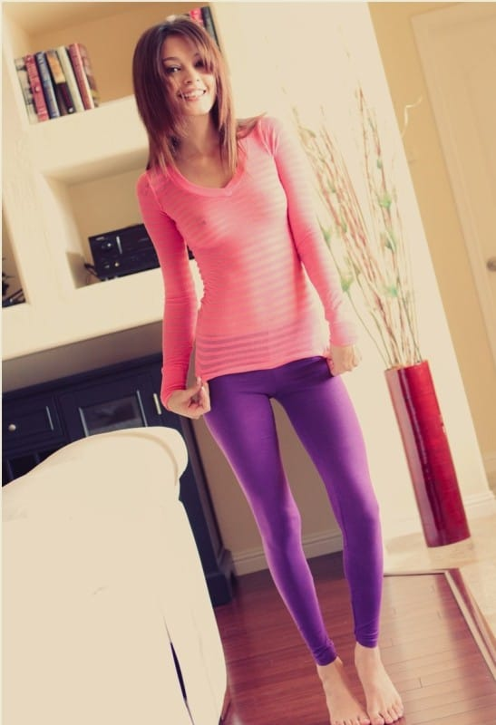 Gina in pink top and blue pants standing up.